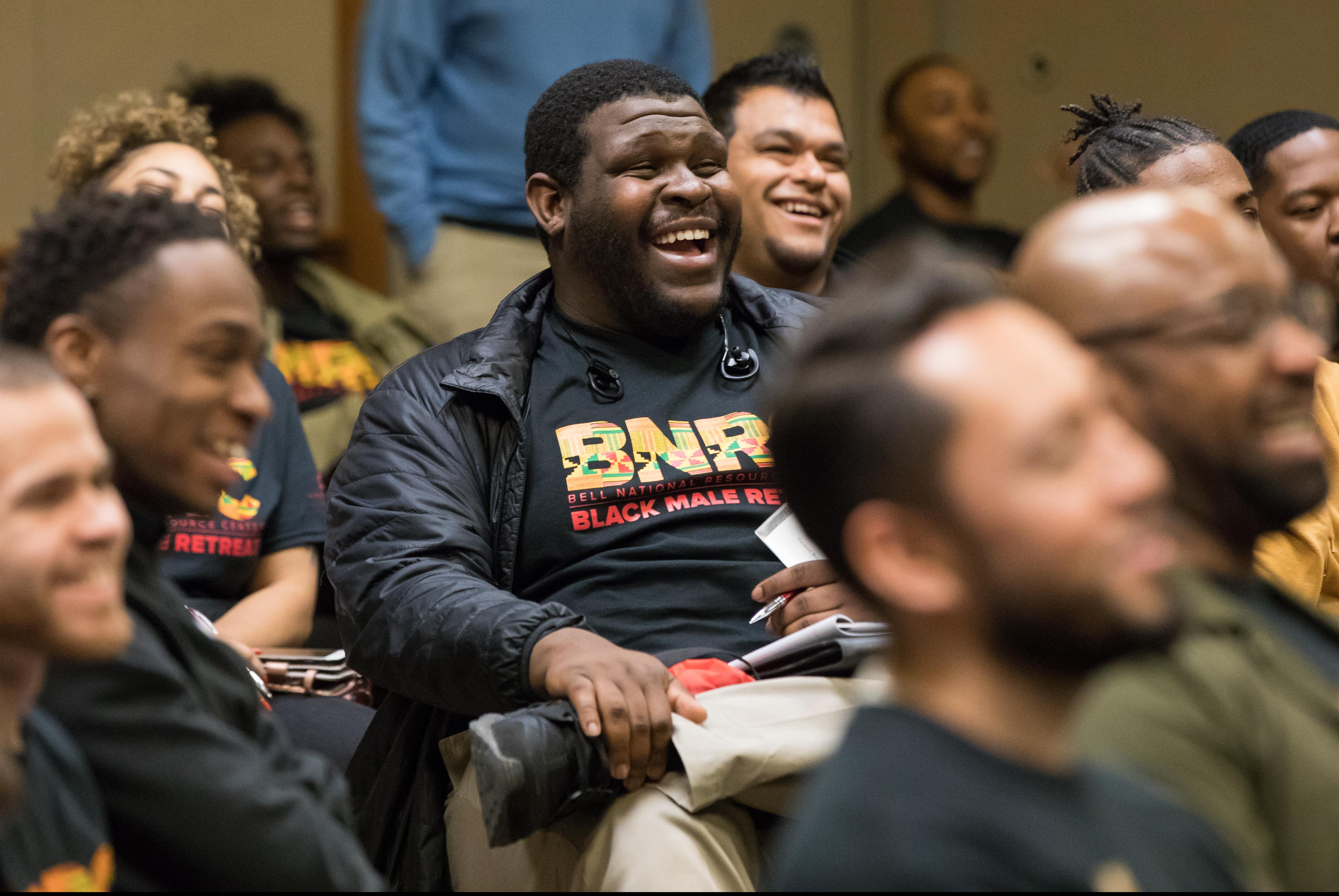 Black male in BNRC retreat shirt laughing into camera