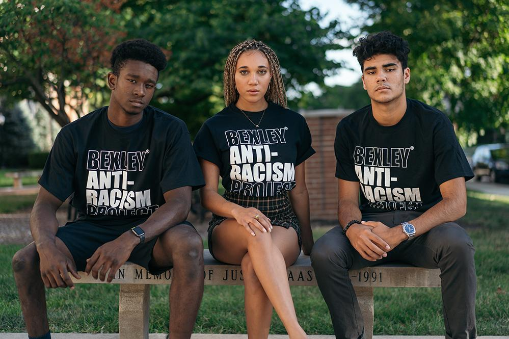Austin, Kaia and Max sitting on a bench with Bexley anti-racism t-shirts