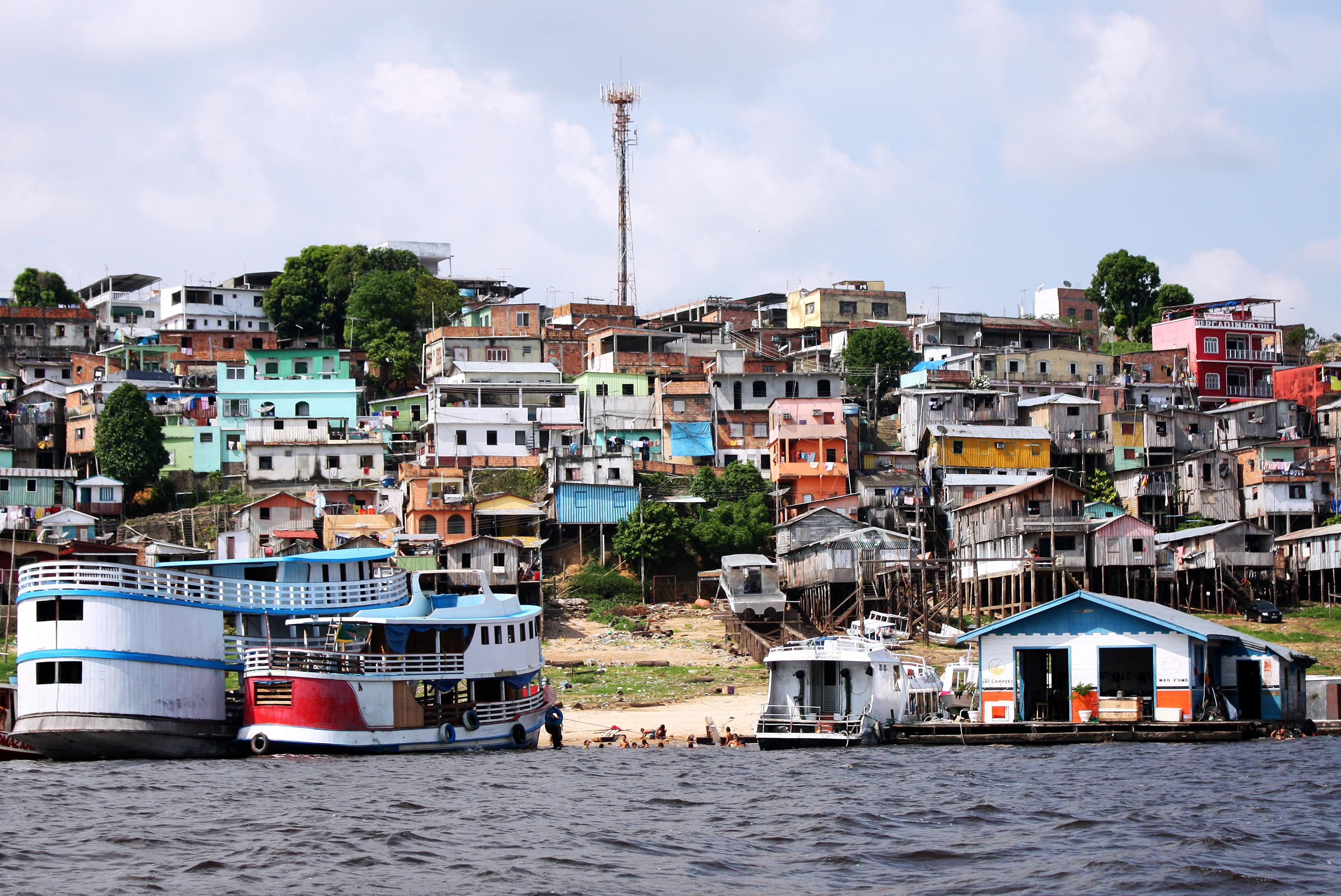 Boats in a harbor in Brazil with colorful houses in the background on hills