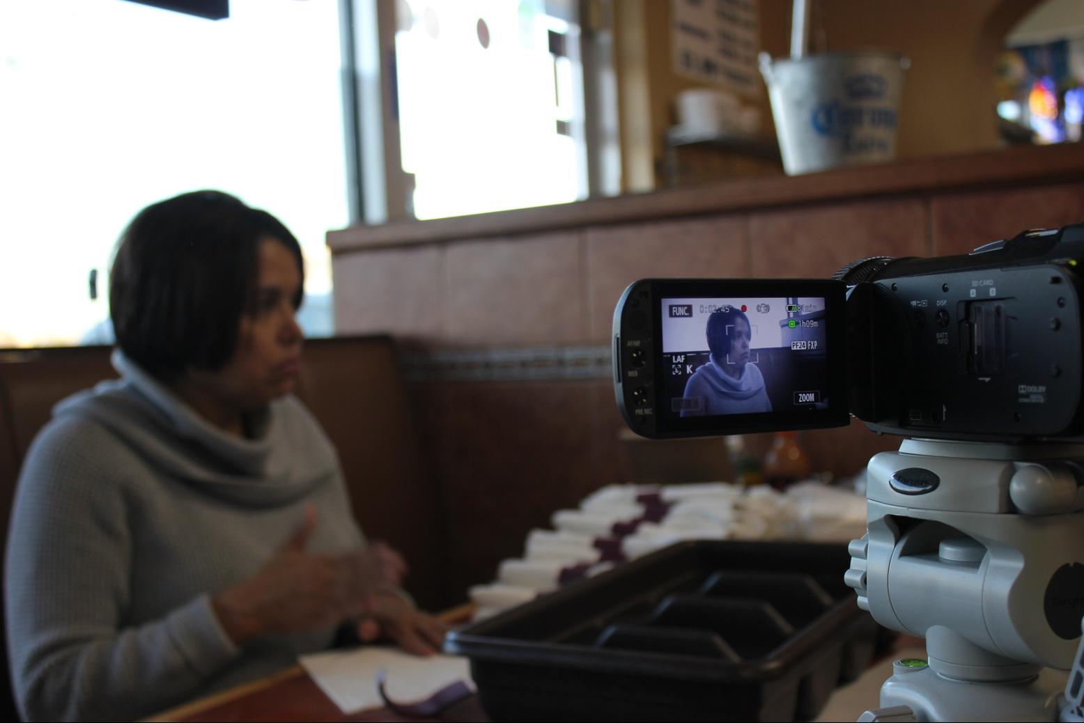 Woman being recorded by a video camera as she speaks.
