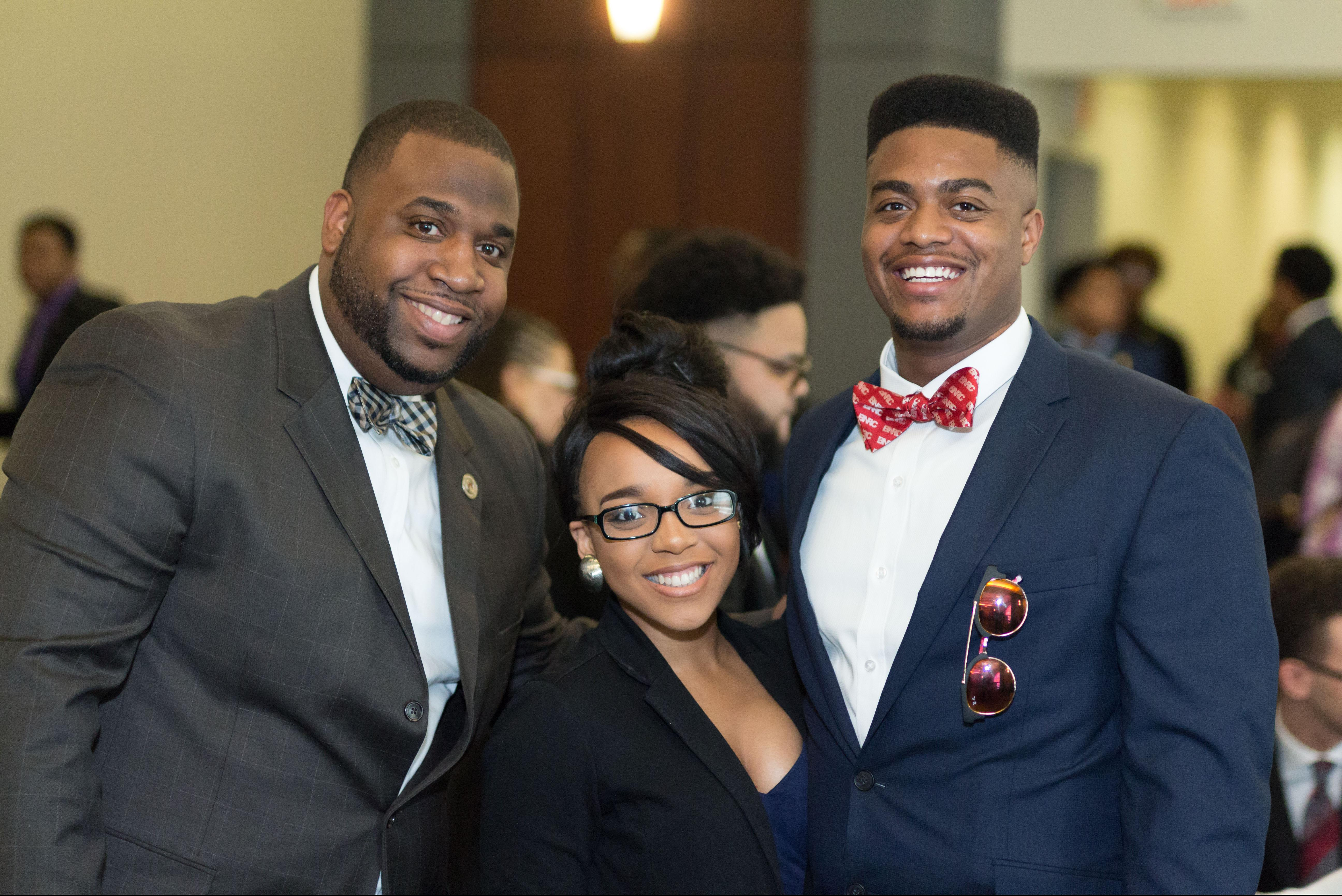 Two Black men and one Black woman smiling at the camera
