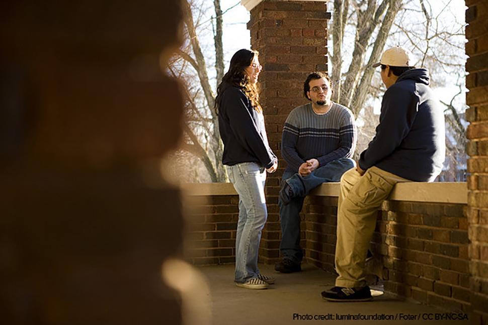 Students sitting under balcony talking