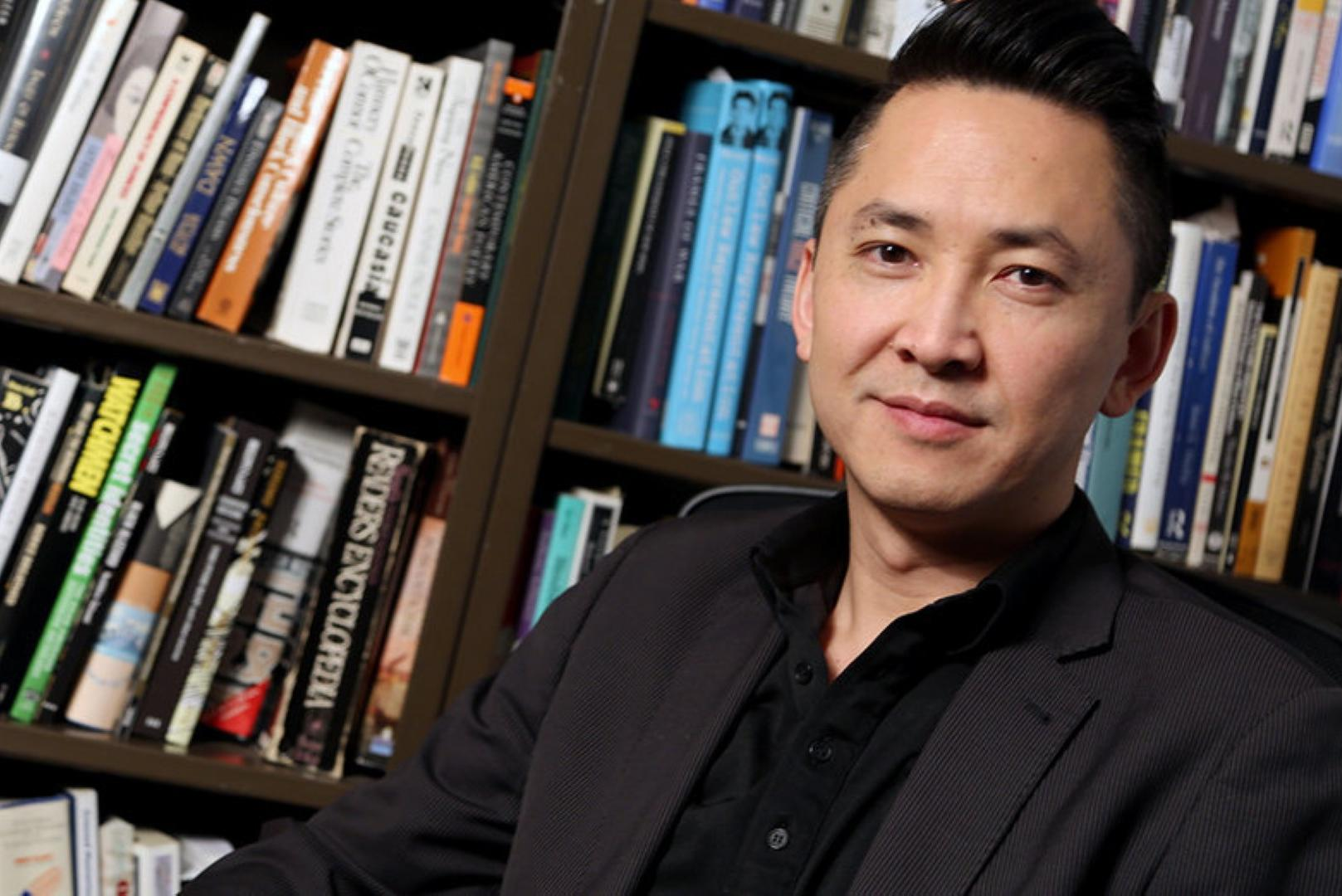 Viet Thanh Nguyen sitting in front of books