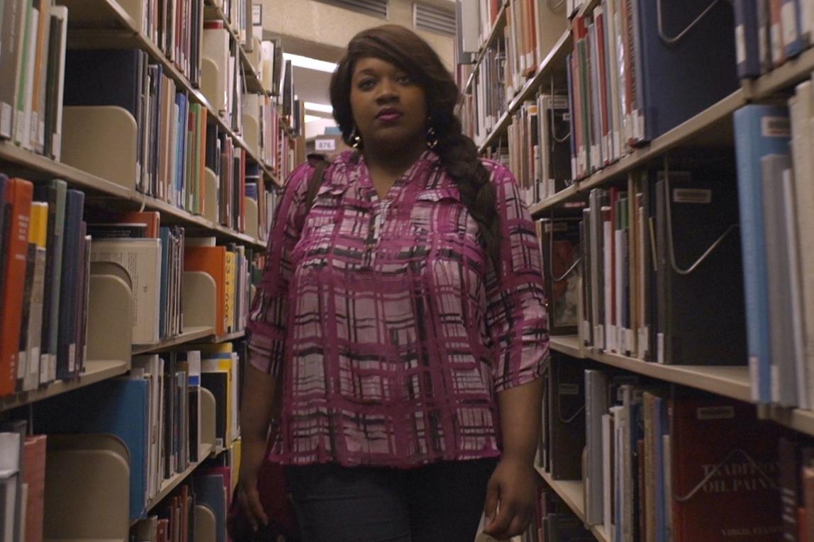 Black girl standing in library shelves
