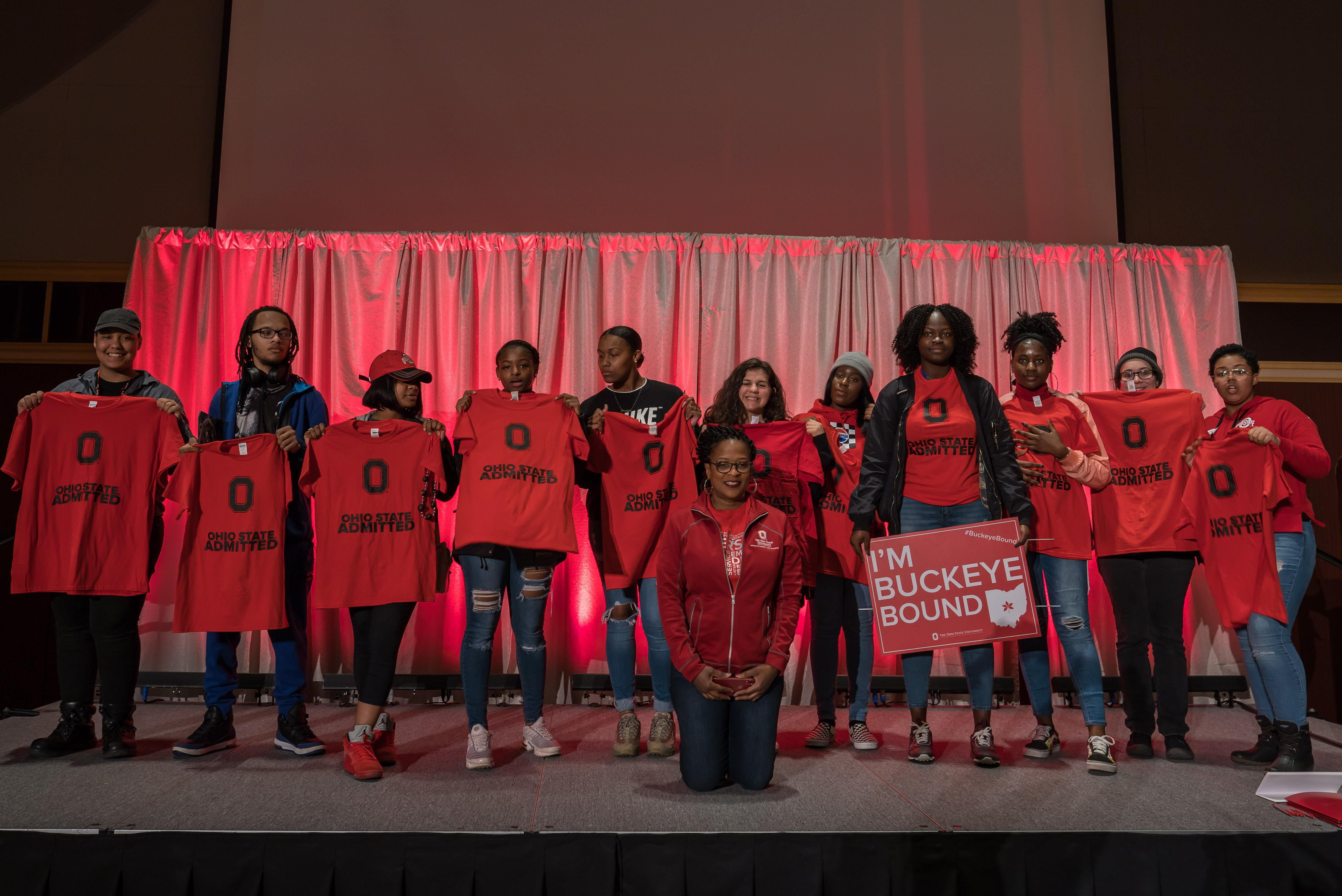 New Young Scholars standing on a stage wearing YSP t-shirts