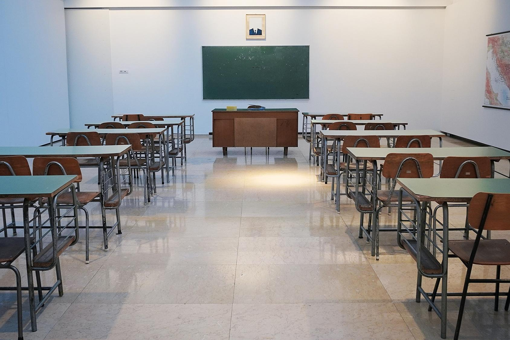 Classroom with desks and blackboard and teacher's desk