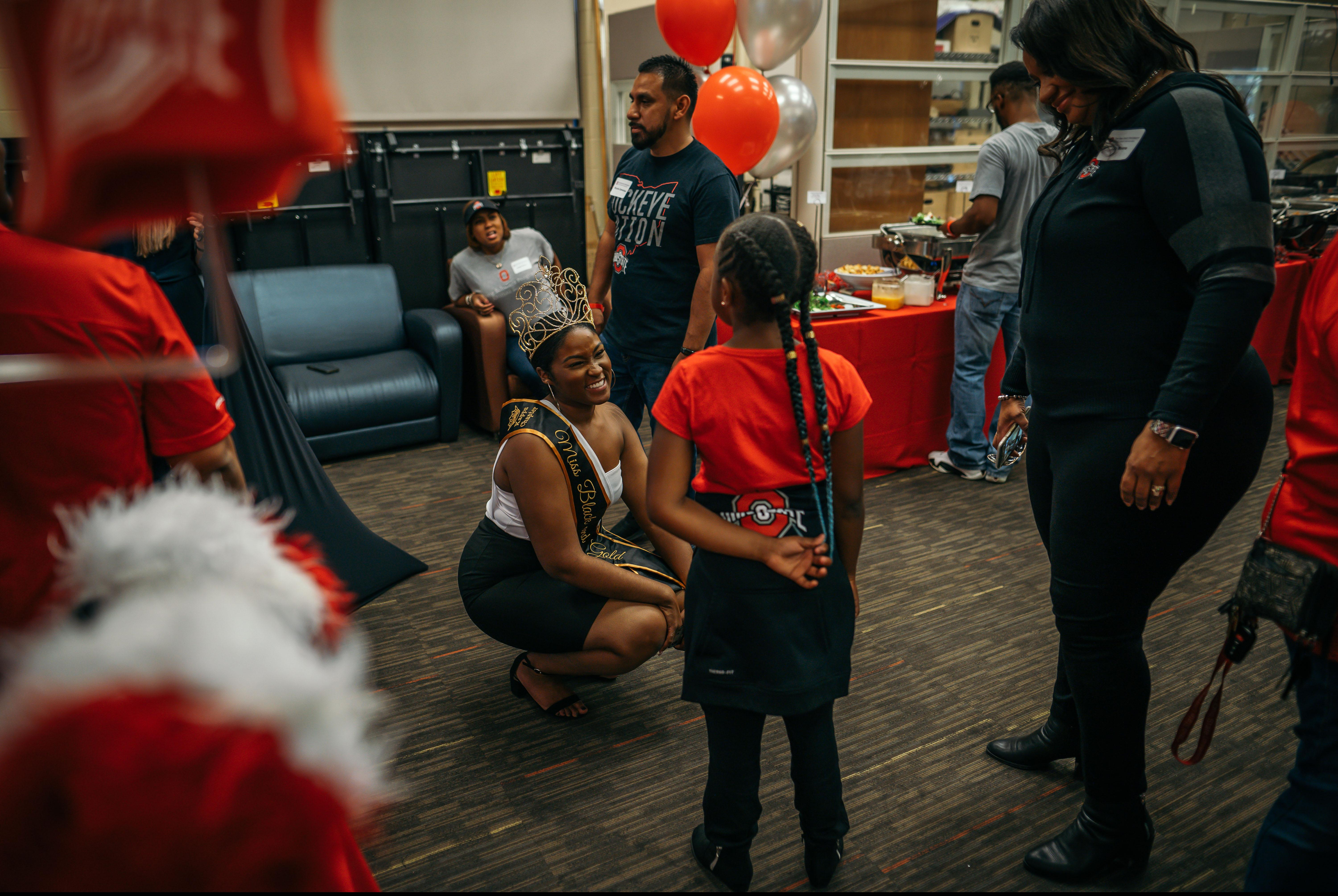 Black Homecoming queen speaks to young child