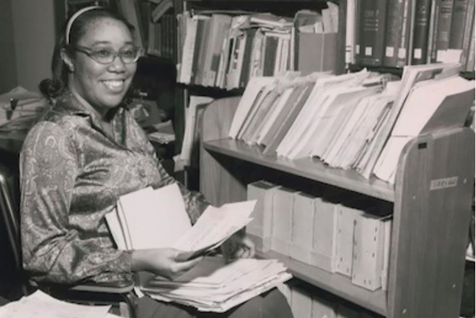 A black and white photograph depicts a smiling, young Black woman seated in a wheelchair. Jean Williams wears a patterned blouse, solid pants, glasses, and a head band. Jean is seated in front of a large bookshelf with many books and papers. She is leafing through a stack of papers on her lap.