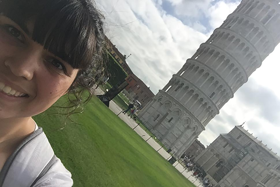 Maekenize Alba taking a photo with the Leaning Tower of Pisa in the background.