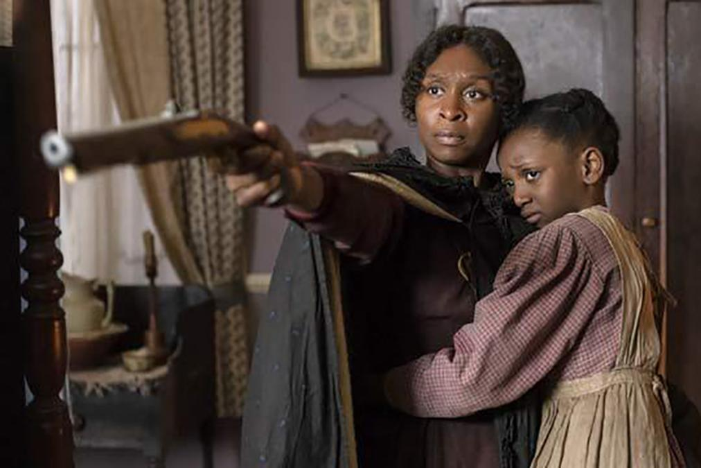 Black women holding a girl and pointing a gun