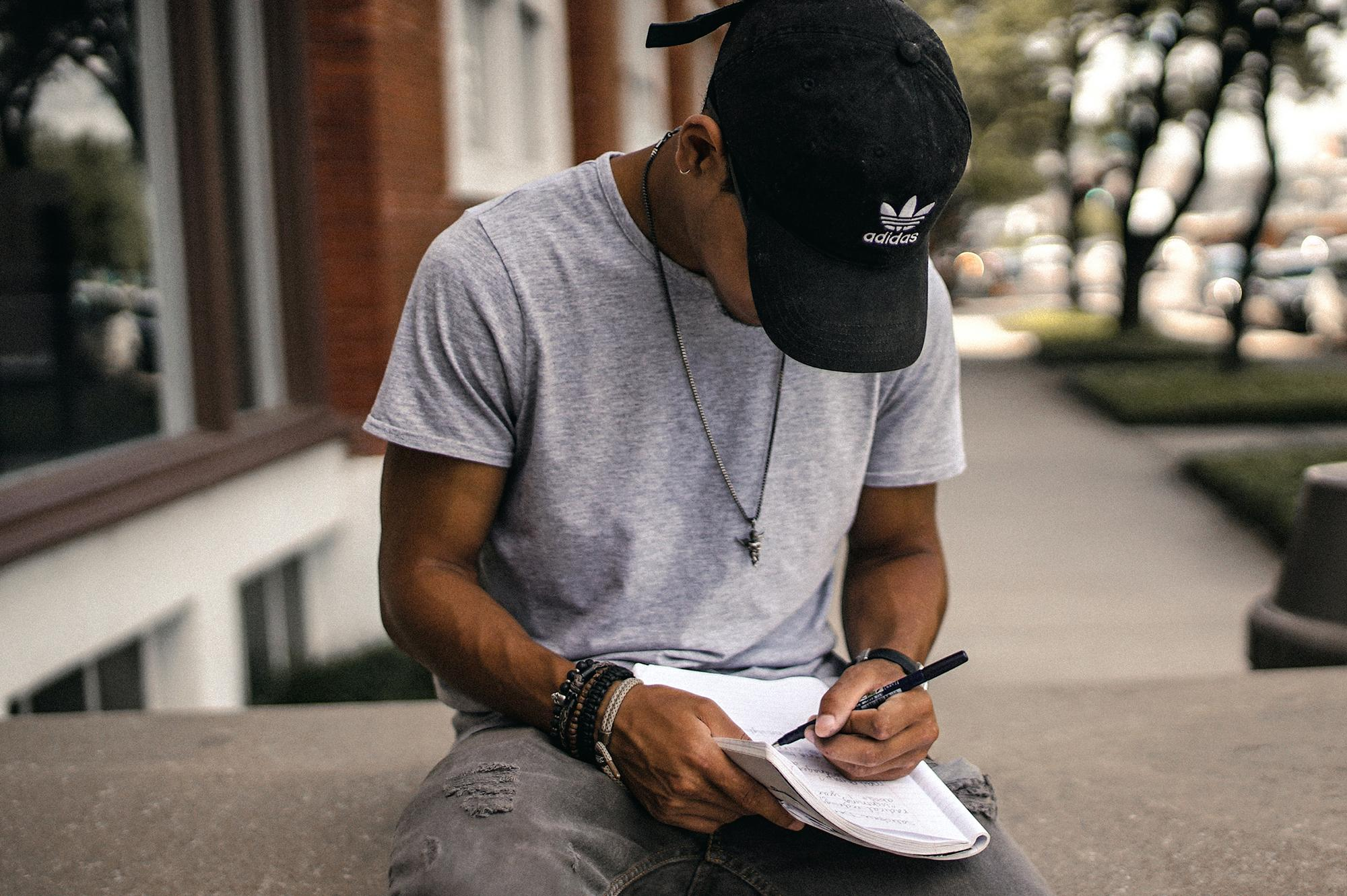 Young Black male writing in a notebook.